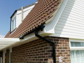 Photograph of a new car port roof attached to new white fascias and soffit and white bargeboards in Kirby Cross