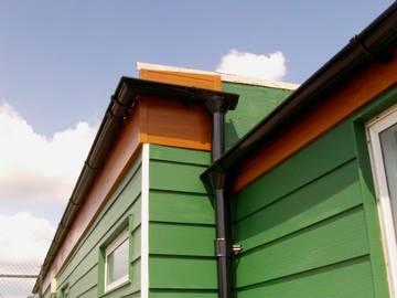 Photograph of Parkside Pine HardiePlank cladding with black Lindab galvanised steel guttering on a school in Kirby Cross