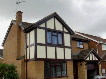 Photograph of Woodgrain soffits and fascia with brown squareline guttering on a detached house in Clacton-on-Sea